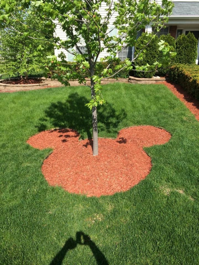 diseño jardines, forma de la cabeza de Mickey en el césped verde con árbol dentro plantado
