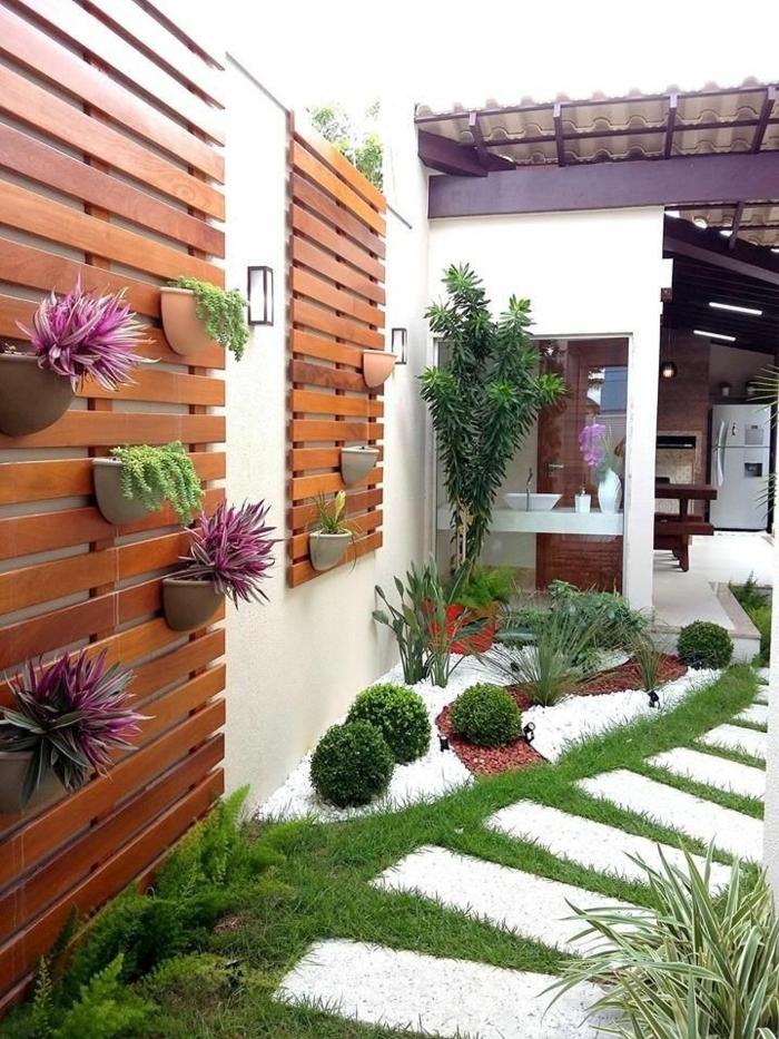 ideas para jardines, encaminamiento con mramor cuadrado en blanco y pared con flores colgadas