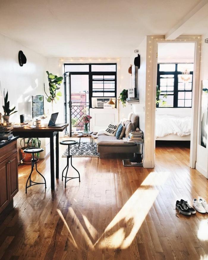 decoracion salon comedor rectangular con mucha luz y sofa con cojines con inscripciones