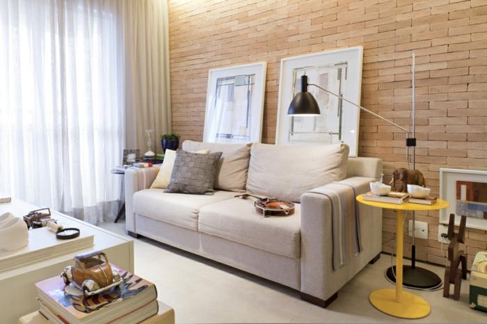decoracion de pisos pequeños, sofa de doble asiento en color crema y mesa pequeña en amarillo
