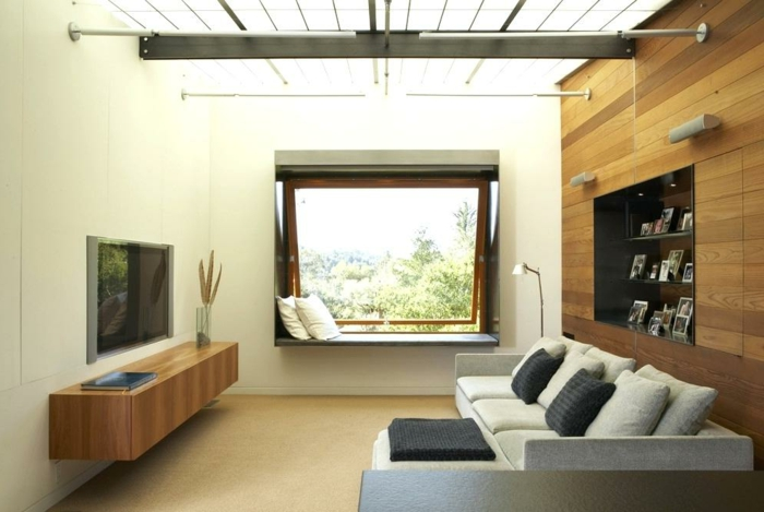 decoracion de pisos pequeños, sofa en gris claro con cojines en negro y con televisor en la pared