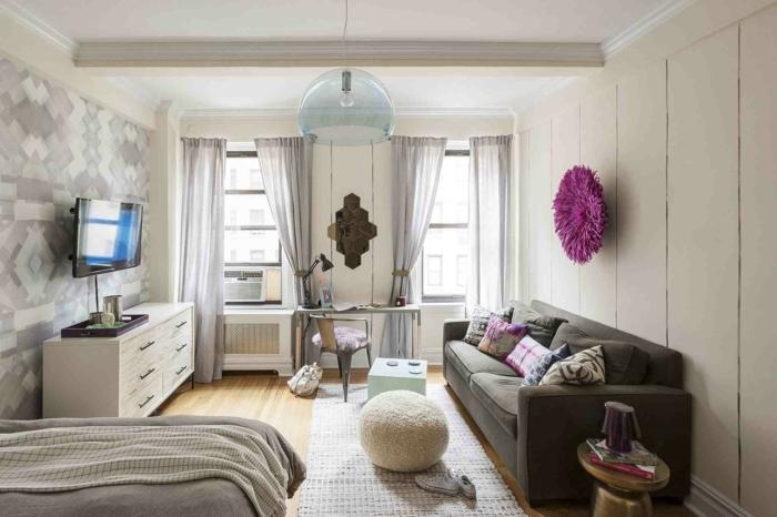 sofas pequeños, salon con otomana de pelo en beige, sofa gris oscuro y televisor en la pared