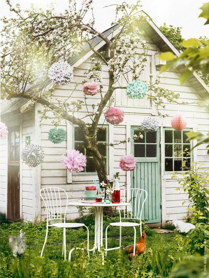 ideas para jardines, casa rústica en blanco con puerta en azul con árbol decorado con flores de papel