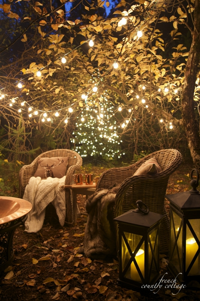 ideas para jardines, estilo romántico con muchas luces colgadas del árbol y sillas de ratán con cojines y mantas
