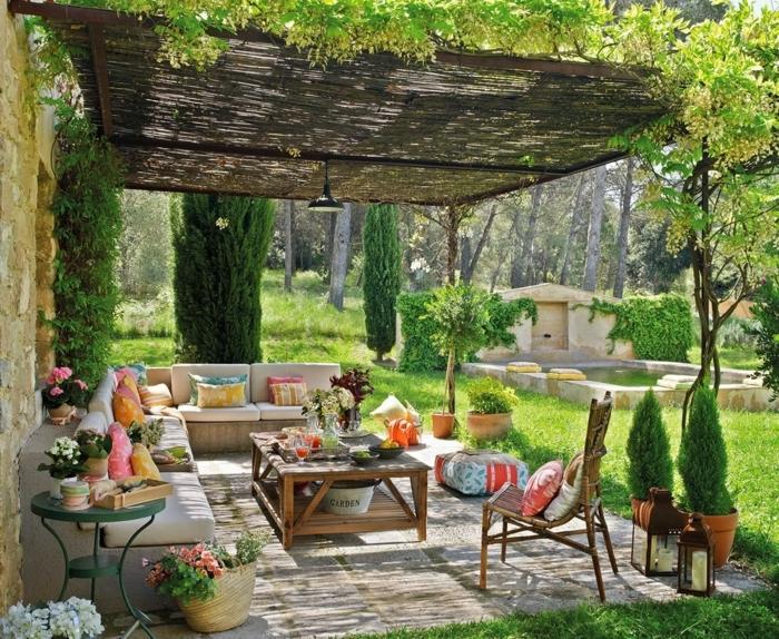 ideas para decorar jardines, jardín cubierto con costruccion de maderas y decorado con muchos cojínes en el sofa