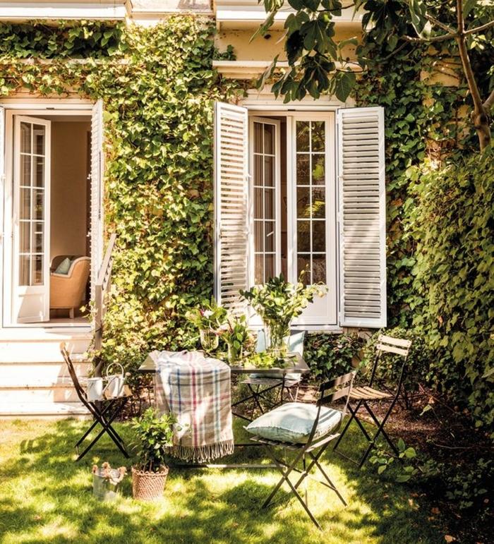 ideas para jardines, mesa y sillas de madera y hierro en el césped, adornadas con jarrones con flores en la mesa