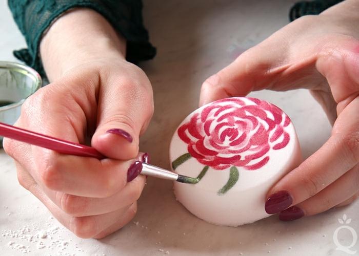 precioso dibujo de rosa sobre un jabón blanco de forma oval, como hacer jabones artesanales paso a paso