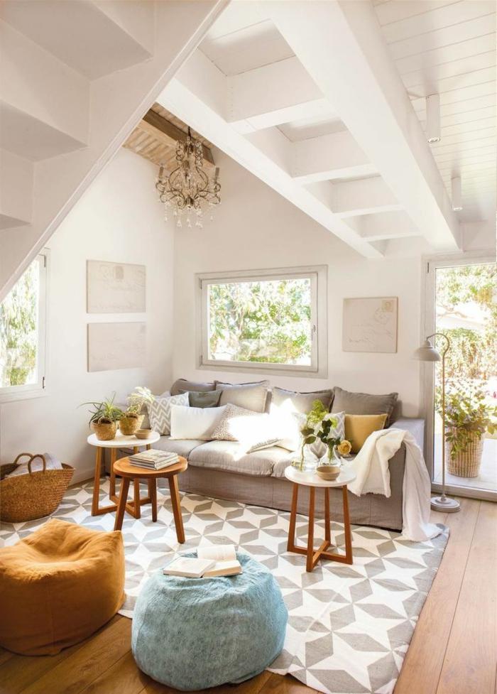 sofas pequeños, sala con mucha luz de pared blancas, muchas ventanas y alfombra con figuras geometricas