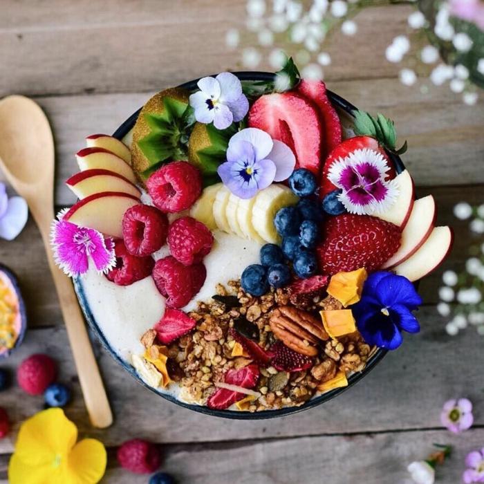 desayuno de dieta con muchas frutas, batido de plátano con frambuesas, fresas, manzanas, kiwi, arándano y cereales