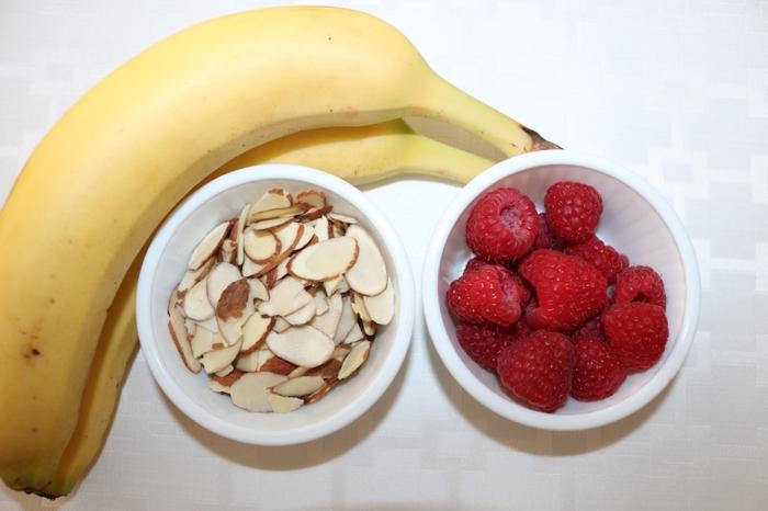 productos necesarios para hacer un smoothie lleno de vitaminas, plátanos, frambuesas y almendras crudas