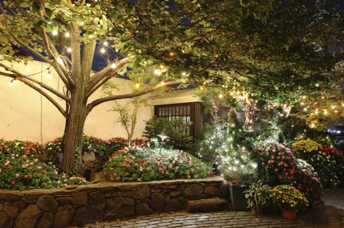 ideas para decorar jardines, jardín con muhas flores de arbusto decorados con muchas luces