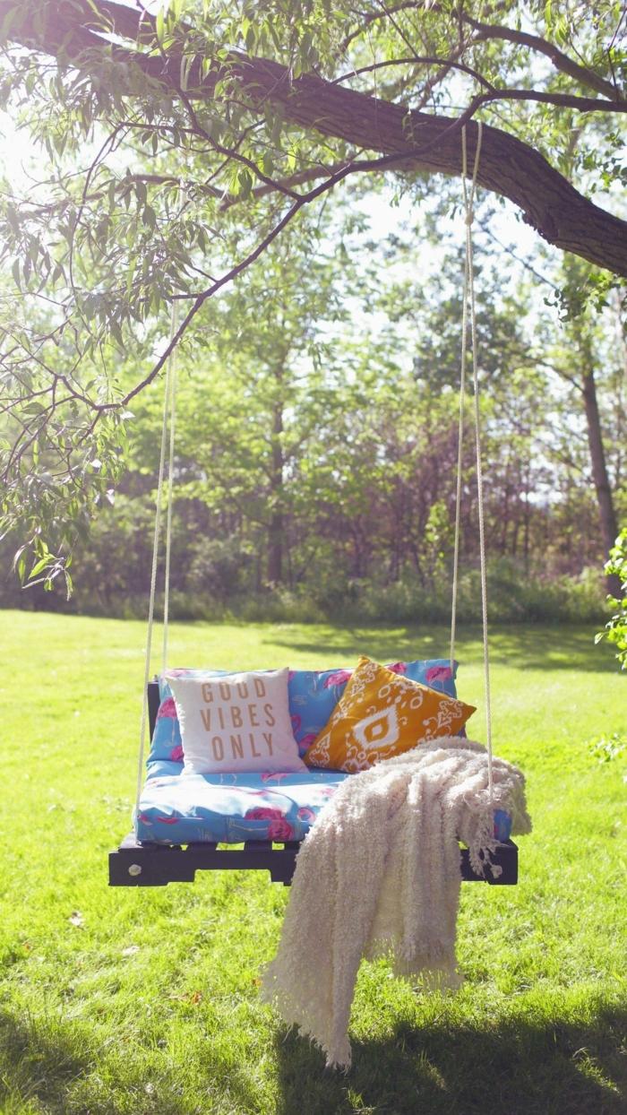 ideas para jardines, columpio de paletas con almahada good vibes only y manta blanca
