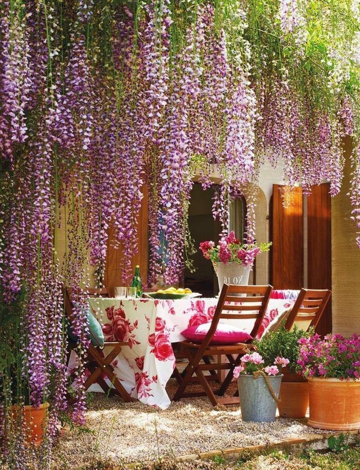 decoracion jardin, mesa con mantel blanco con flores grades rosas y cubo de flores vivas en la mesa