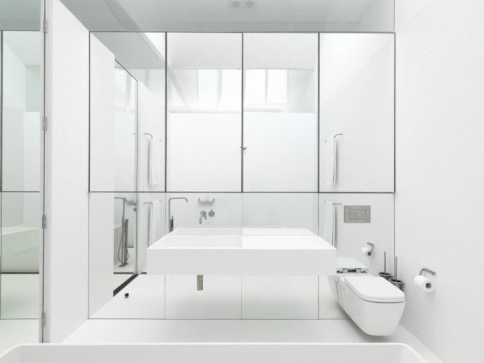 baño minimalista decorado en blanco, aseos pequeños tendencias decoración moderna, muchos espejos efecto óptico