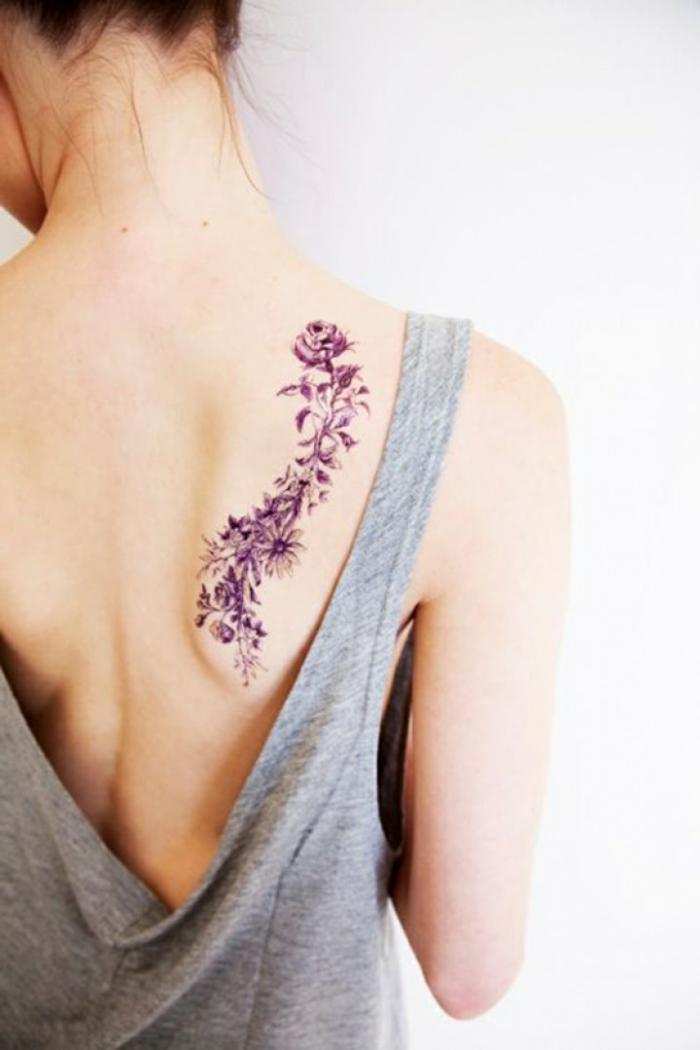 ideas de tatuajes con motivos florales, preciosas flores en morado en la espalda, tatuajes pequeños con significado
