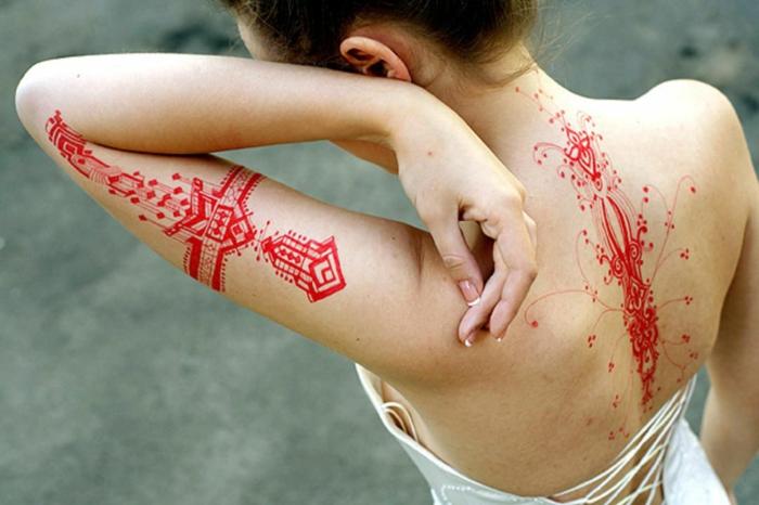 ejemplos de tatuajes simbolicos con figuras geométricas, precioso tatuaje en el brazo y en la espalda en rojo