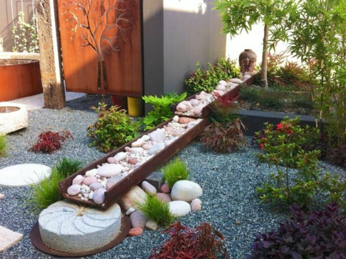 ideas para decorar jardines en estilo zen, suelo con gravilla en color oscuro, decoración de piedras y canto rodado