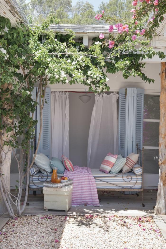 decoracion de jardines con piedras, cama vieja de hierro utilizada como sofá para decorar el jardín