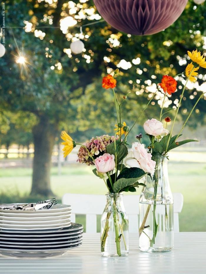 decoracion de jardines con piedras, jarrones de vidrio con flores vivas para la mesa del jardín