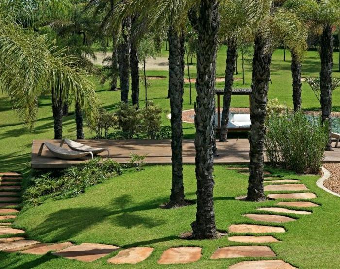 ideas para jardines, jardín exótico con palmeras y hamacas y con encaminamiento de piedras en el césped