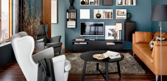 sofas pequeños, salon con pared oscura en azul y sillones grandes no pegados a la pared