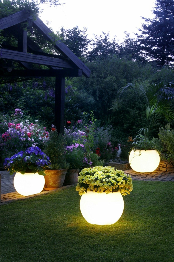 ideas para jardines, lámparas de suelo redondas, grandes, decoras con flores en el césped