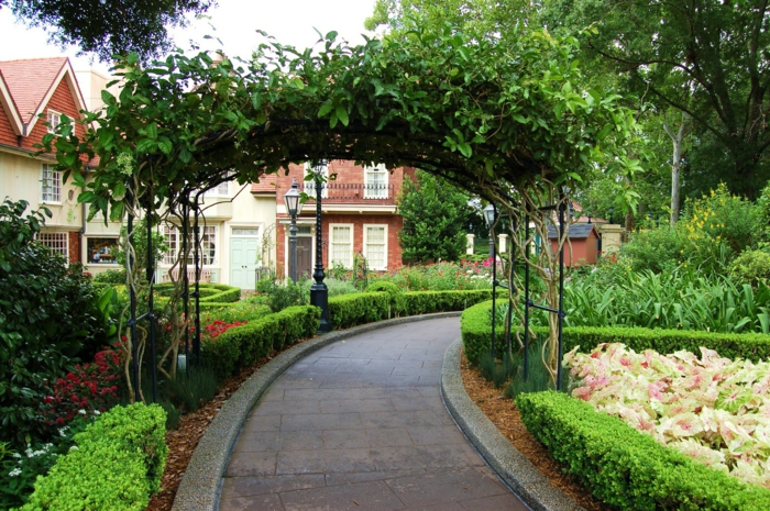 decoracion patios exteriores, arco de hierro decorado con plantas colgantes y césped dividido en diferentes áreas