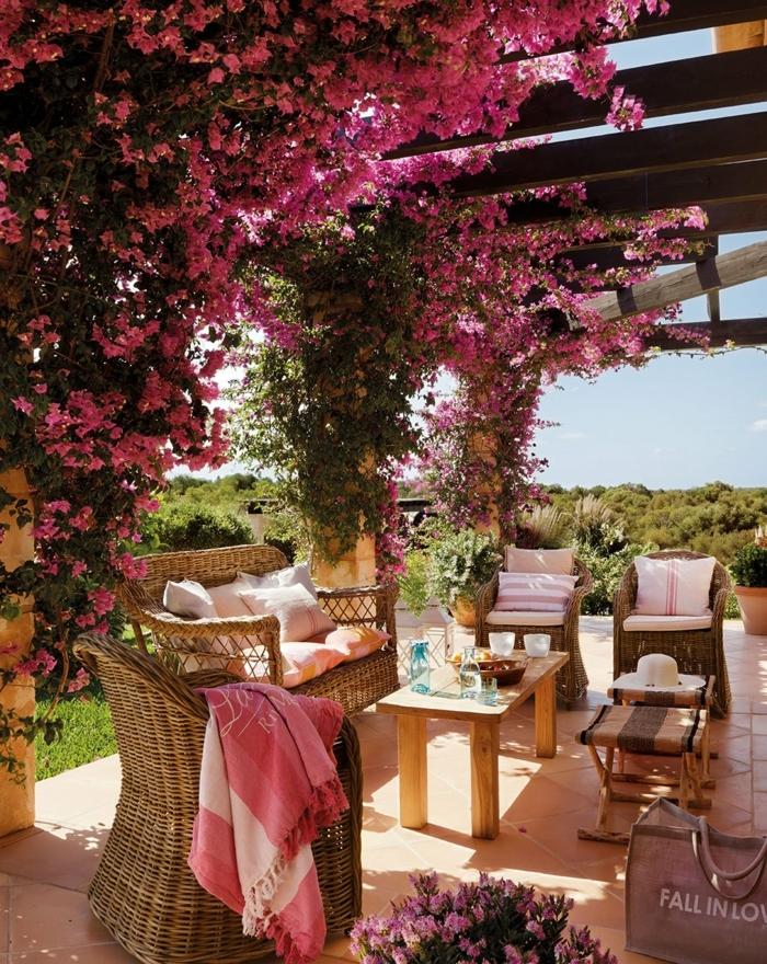 decoracion de jardines, sitio para pasar el rato con mubles de ratán decorado con flores colgantes en rosa