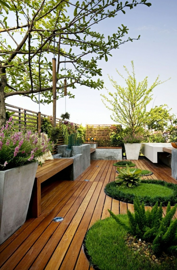 decoracion patios exteriores, jardñin con céspedes redondos y suelo de madera con macetas grandes