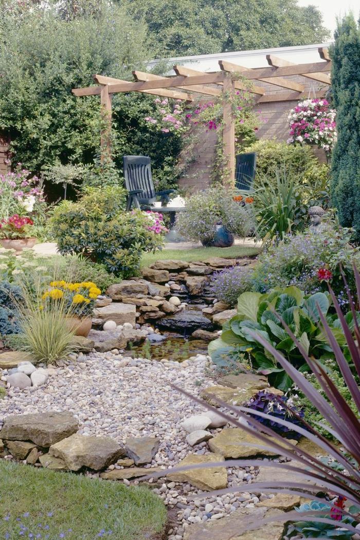 preciosa decoración de un jardin mediterraneo, canto rodado, piedras, rocallas y una pérgola de madera