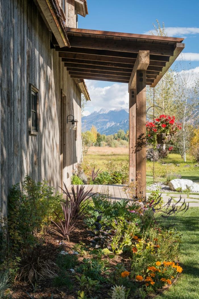 ideas de decoración jardines pequeños en estilo rústico, macetas colgantes con flores en rojo