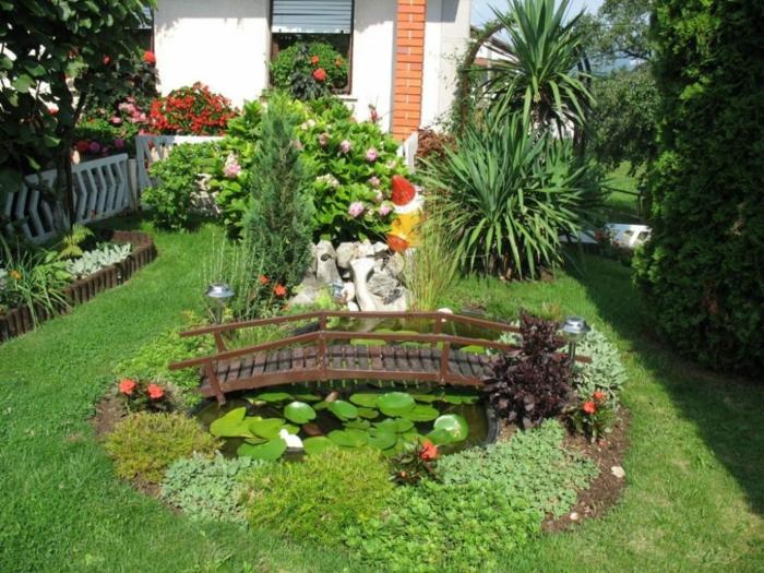 jardin mediterraneo consejos e ideas de decoración, pequeño jardín con césped y pequeño puente de madera