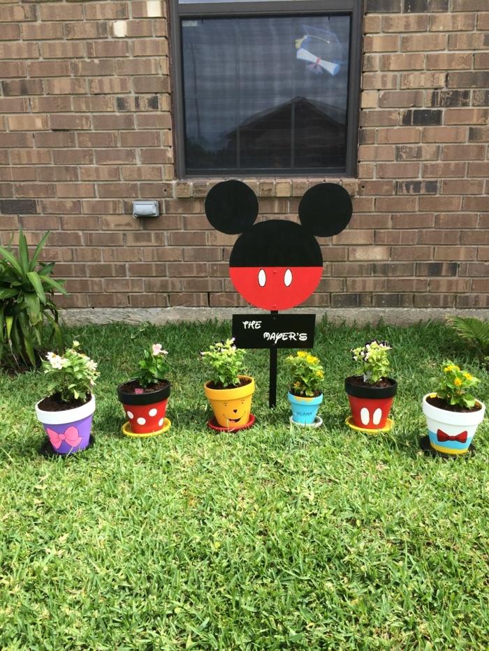 decoracion de jardines rústicos, macetas pintadas de Disney en el césed, diferentes tamaños