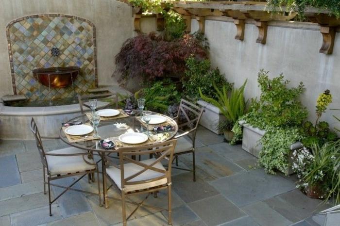 decoracion de jardines rústicos, mesa con sillas de hierro y mesa de hierro y cristal con fuente de agua