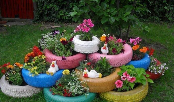decoracion de jardines rústicos, decoración con naumáticos de diferentes colores y con flores plantadas dentro