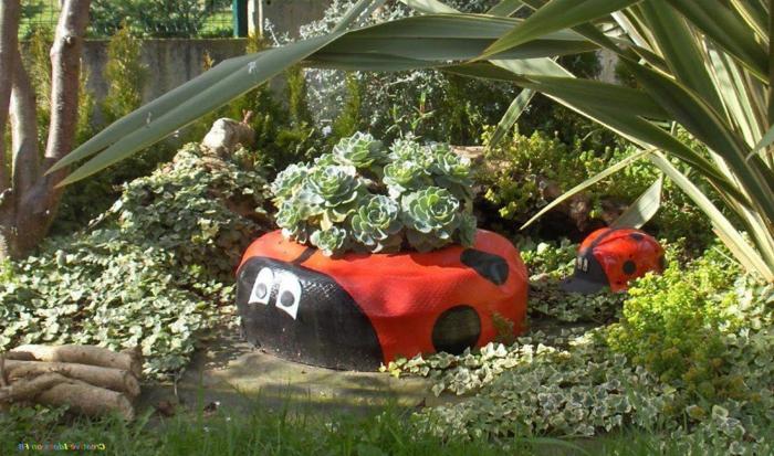 decoracion de jardines rústicos, neumático de mariquita con plantas plantadas en el césped