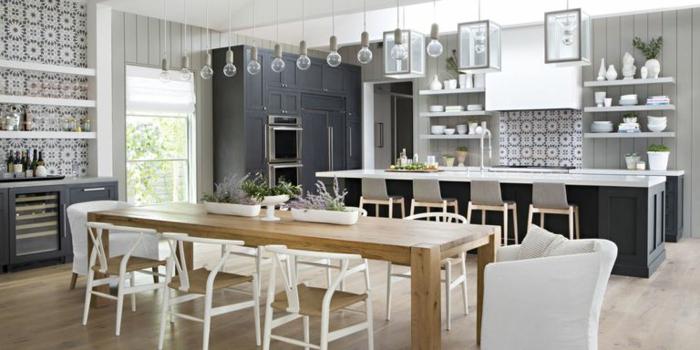 cocina con mesa grande para mucha gente en color marrón claroo con sillas y sillones blancos