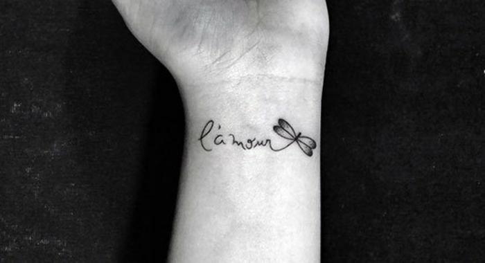 precioso tatuaje minimalista en la muñeca, diseño delicado con letras y dibujo de libelula, tatuajes de amigas
