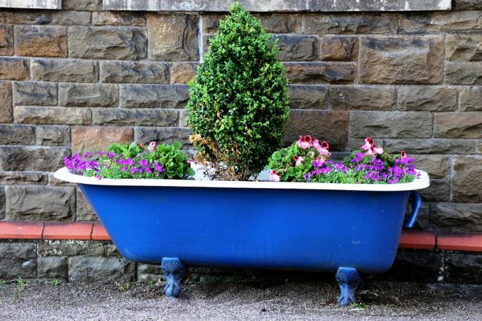 ideas de decoración jardines pequeños, bañera pintada en azul con flores y arbustos, ideas DIY de encanto