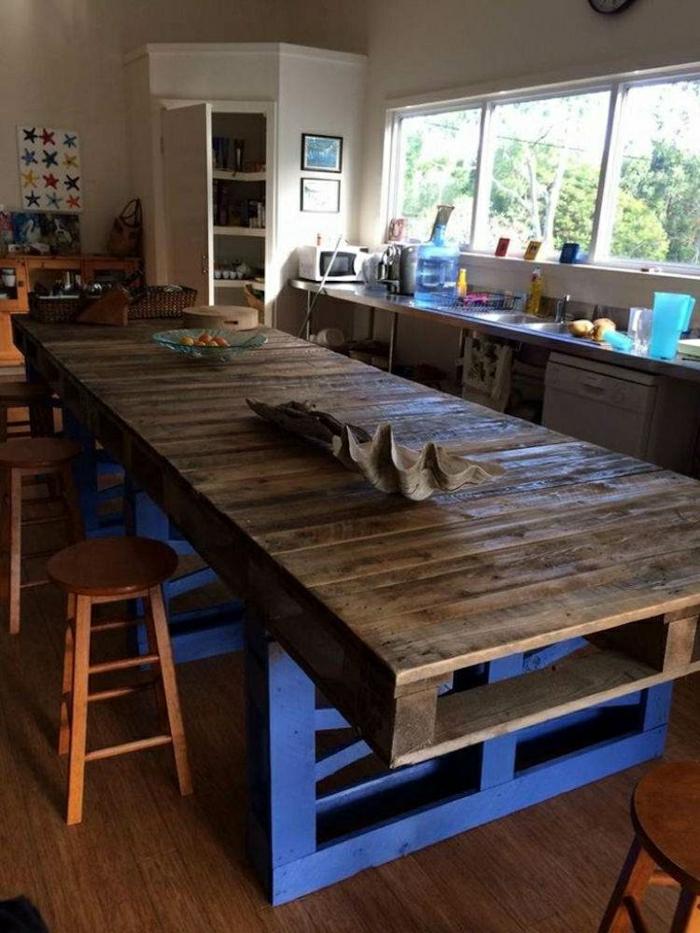 mesa grandehecha con cuatro palets pitados de marron y con patas gruesas en azul, manualidades con palets