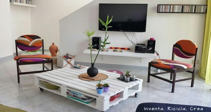 mesa blancade palet con ruedas negras, decorada con macetas pequeñas de colores y un bambú en el medio