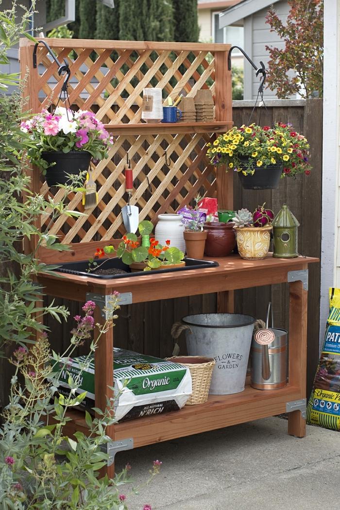 decoracion de jardines rústicos, mesa de madera para poner los cacharros del jardín, con macetas con flores