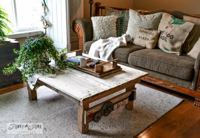 un modelo más incomún de mesa con palets con patas de madera y con decoraciones vintige al lado