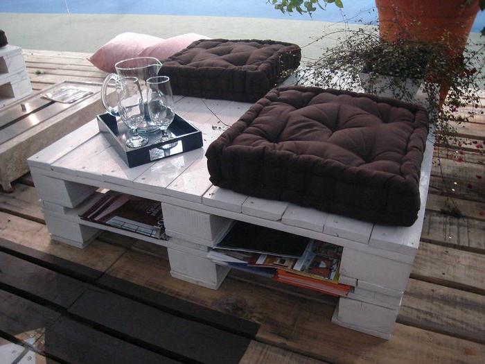 mesa de palets en color blanco, dos palets puestos uno encima del otro con cojínes gruesos en marrón y rosa