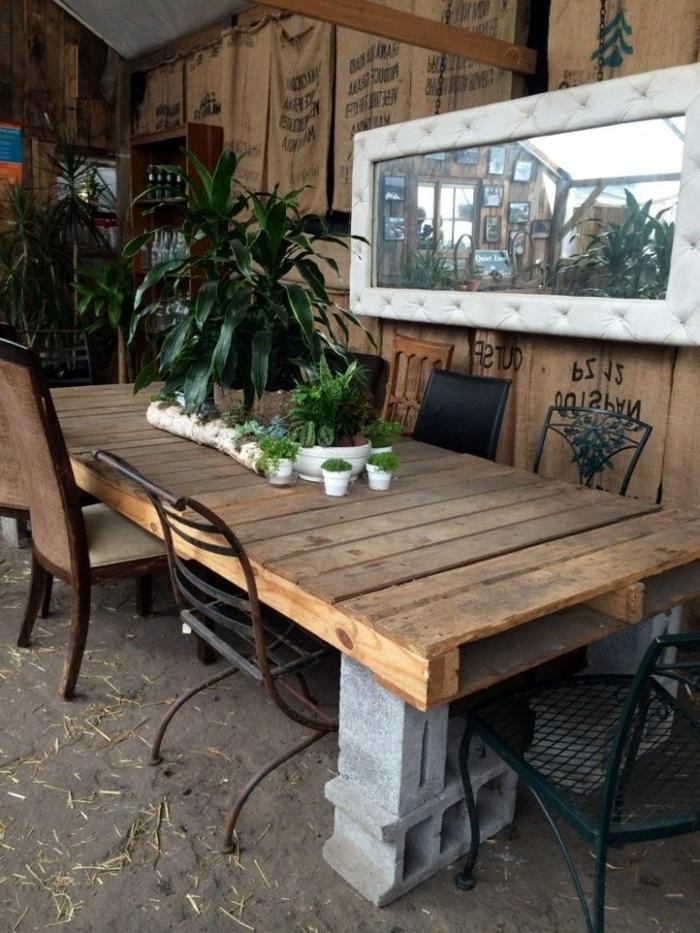 mesa de palets con tres palets lijados, sin pitar con bloques de yeso haciendo de patas, plantas encima