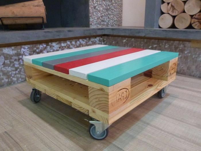 pequeña mesa de palets con ruedas, la superficie está pintada de color azul claro, blanco, rojo y gris