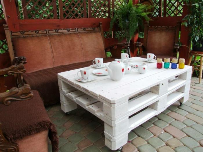 mesa de palets en blanco pintada compuesta por dos palets con tazas de té en blanco con tulipanes