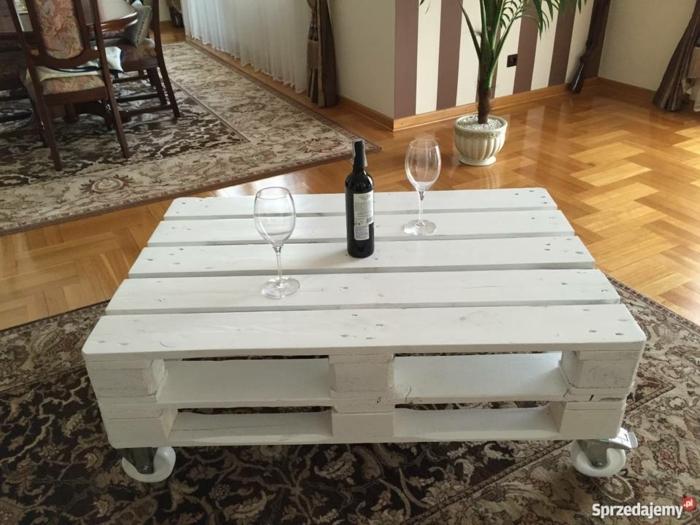 mesa de dos palets pintada de pintura blanca con ruedas con espacio paa revistas y con botellas encima