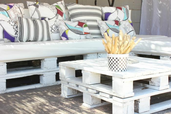mesa para el jardín hecha de palets, pintade de color blanco, sofá de palets con cojínes multicolores