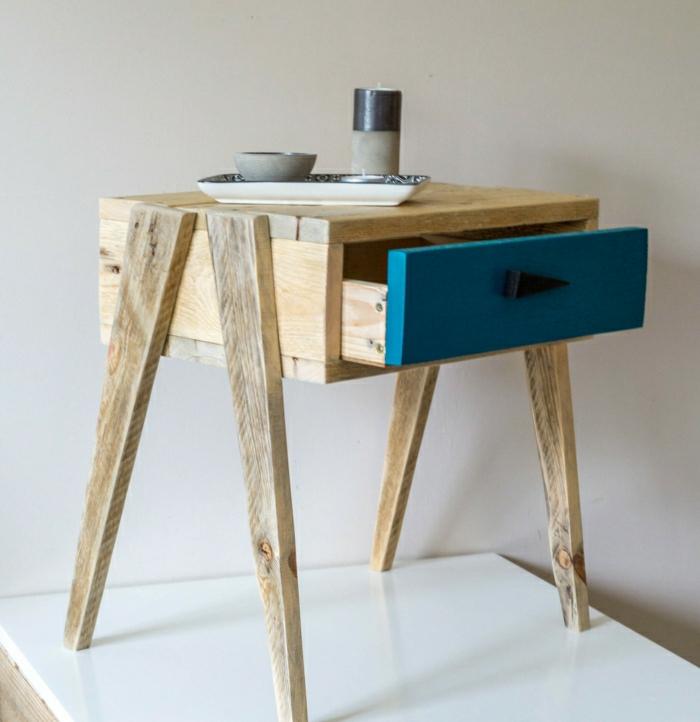 mesa pequeña de palets con patas de madera y con cajón pintado de azul, con vela encima de ella